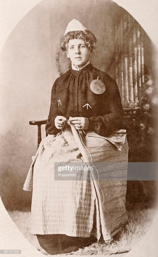 Suffragette Emily Hayes Duval, a prisoner at Holloway Prison in London, in prison uniform and sewing mail bags, circa 1908. (Photo by Popperfoto/Getty Images)